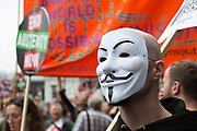 London, UK. Saturday 20th June 2015. People's Assembly against austerity demonstration through Central London. 250,000 people gathered to protest in a march through the capital protesting against the Tory cuts, holding placards and banners. Anonymous mask.
