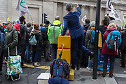 Businessmen and financiers look at environmental activists protesting about Climate Change during the blockade outside the Bank of England in the heart of the capitals financial district, the City of London aka the Square Mile, on the seventh day of a two-week prolonged worldwide protest by members of Extinction Rebellion, on 14th October 2019, in London, England.