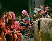 A woman breastfeeding with her family around. Family life in a Wakhi home. The traditional life of the Wakhi people, in the Wakhan corridor, amongst the Pamir mountains.