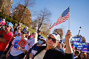 """07 NOVEMBER 2020 - DES MOINES, IOWA: A person wearing a Q-Anon hat waves an American flag during a """"Stop the Steal"""" rally at the Iowa State Capitol. There were rival election rallies at the State Capitol in Des Moines Saturday. About 1,000 supporters of President Donald Trump gathered on the steps of the State Capitol and called for an end to vote counting. About 300 supporters of President Elect Joe Biden gathered in People's Plaza, on the south lawn of the Capitol, and called for the vote count to continue until every vote was counted.     PHOTO BY JACK KURTZ"""