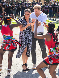 """File photo dated 23/09/19 of the Duke and Duchess of Sussex meeting a group of dancers at the Nyanga Township in Cape Town, South Africa, on the first day of their tour of Africa. The royal couple have announced they are to """"step back"""" as senior members of the royal family and will now divide their time between the UK and North America."""