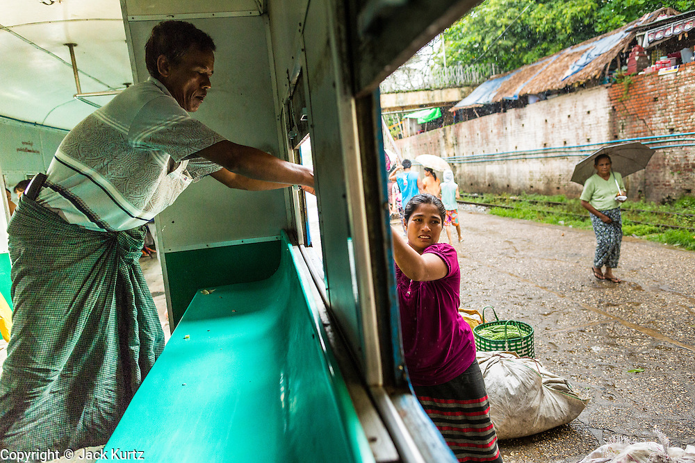 15 JUNE 2013 - YANGON, MYANMAR:  A woman helps her husband get their stuff of the Yangon Circular Train as it pulls into their station. The Yangon Circular Railway is the local commuter rail network that serves the Yangon metropolitan area. Operated by Myanmar Railways, the 45.9-kilometre (28.5mi) 39-station loop system connects satellite towns and suburban areas to the city. The railway has about 200 coaches, runs 20 times and sells 100,000 to 150,000 tickets daily. The loop, which takes about three hours to complete, is a popular for tourists to see a cross section of life in Yangon. The trains from 3:45 am to 10:15 pm daily. The cost of a ticket for a distance of 15 miles is ten kyats (~nine US cents), and that for over 15 miles is twenty kyats (~18 US cents). Foreigners pay 1 USD (Kyat not accepted), regardless of the length of the journey.     PHOTO BY JACK KURTZ