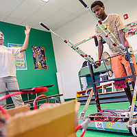 040214       Cable Hoover<br /> <br /> Danielle Hutchinson, left, and Manasse Koffi demonstrate their competition model robot at the Boys and Girls Club in Gallup Wednesday.