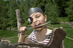 Portrait of a girl dressed up as a pirate biting saber in playground, Bavaria, Germany