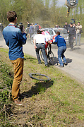 France, April 13th 2014: A spectator uses his mobile to capture the action as Alexander Kristoff, Team Katusha, rejoins the race following a wheel change during the 2014 Paris Roubaix cycle race.