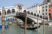 """Gondoliers row gondolas on the Grand Canal under Rialto Bridge (or Ponte di Rialto, built 1591), which is the oldest of four bridges spanning the Grand Canal in Venice, Italy, Europe. The single span stone bridge designed by Antonio da Pontestone is an architectural icon of Venice. In 452 AD, Attila the Hun invaded Italy, and people retreated to offshore islands called Rivo Alto (high bank), or Ri'Alto, the center of Venice. Venice/Venezia is the capital of Italy's Veneto region, named for the ancient Veneti people from the 900s BC. The romantic """"City of Canals"""" stretches across 100+ small islands in the marshy Venetian Lagoon along the Adriatic Sea in northeast Italy. The Republic of Venice was a major maritime power during the Middle Ages and Renaissance, a staging area for the Crusades, and a major center of art and commerce (silk, grain and spice trade) from the 1200s to 1600s. The wealthy legacy of Venice stands today in a rich architecture combining Gothic, Byzantine, and Arab styles. Venice and the Venetian Lagoons are on the prestigious UNESCO World Heritage List."""