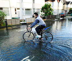 © Licensed to London News Pictures. Date 9 Jan 2014. Oxford. Carrying sandbags on a bike. River Thames floods at Oxford causing the closure of the Abingdon and Botley roads.. Photo credit : MarkHemsworth/LNP