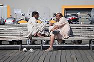 Immigrants conversing on a bench near the port of genoa. Immigrati conversano su una panchina vicino al porto di genova