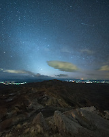 The zodiacal light glowed in the west after sunset before the moon rose. The view was from my campsite in the McCullough Peaks Badlands and the lights are from the edge of Cody.