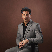 Corporate portrait shot to 3/4 length against brown textured background featuring asian businessman in grey suit fully styled and colour graded to suit customer brand colours