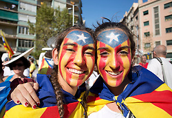 """A pair of young Catalan separatists wear a """"estelada"""" flag makeup as she joins tens of thousands in the centre of Barcelona during 'La Diada', the annual festival to mark National Day of Catalonia, to demand the independence of Catalonia."""
