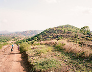 """NUBA MOUNTAINS, SUDAN – JUNE 9, 2018: Travelers pass on foot between Hieban town and Kouda, the cultural center of Hieban County.<br /> <br /> In 2011, the government of Sudan expelled all humanitarian groups from the country's Nuba Mountains. Since then, the Antonov aircraft has terrorized the Nuba people, dropping more than 4,080 bombs on hospitals, schools, marketplaces and churches. Today, vestiges of the Antonov riddle the landscapes of daily life, where more than 1 million Nuba live in famine conditions – quietly enduring the humanitarian blockade intended to drive them out of the region. The skies are mostly clear. Yet the collective memory of the bombings remains an open wound, and the Antonov itself a persistent threat. So frequent were the attacks that the Nuba nicknamed the high flying aircraft and its dismal hum: """"Gafal-nia ja,"""" they would declare, running to the hillsides. """"The loss of appetite has come."""""""