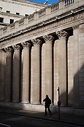 A man walks in front of the Bank of England in what would normally be the morning rush hour in the City of London on March 17th, 2020. The financial district of the UK is unusually quiet after the government requested people to refrain from all but essential travel and activities yesterday.