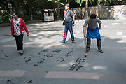 Elerly Chinese men practicing calligraphy on the ground at Huanhua Park, Chengdu, Sichuan, China
