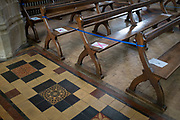 Church seating pews are marked with ticks and crosses marking where parishioners are allowed to sit according to Coronavirus pandemic lockdown guidelines in St. Peter and St. Paul's church, on 9th July 2020, in Lavenham, Suffolk, England. At the moment, indoor religious gatherings are still banned though private prayer is allowed. Completed in 1525, the church is excessively large for the size of the village and with a tower standing 141 ft (43 m) high it lays claim to being the highest village church tower in Britain.