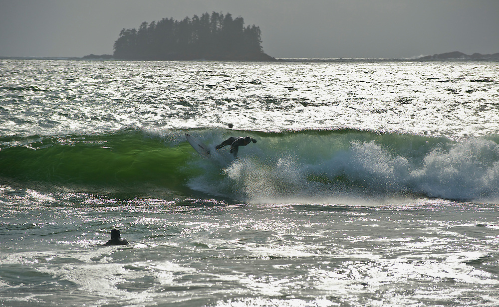 A surfer rides a wave in the cold waters of Sitka, AK Sept 11, 2009.