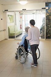 Senior woman in wheelchair with girl in rest home