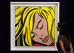 © Licensed to London News Pictures. 12/04/2012. London, UK . A woman stands  in front of Roy Lichtenstein's 'Sleeping Beauty' which is expected to fetch 30 - 40 million US dollars. Photocall for Sotheby's Impressionist and Modern Art Evening Sale 12 April 2012. Photo credit : Stephen Simpson/LNP