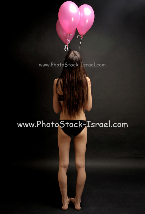 Young 18 year old female teen in black underwear with pink balloons on black background