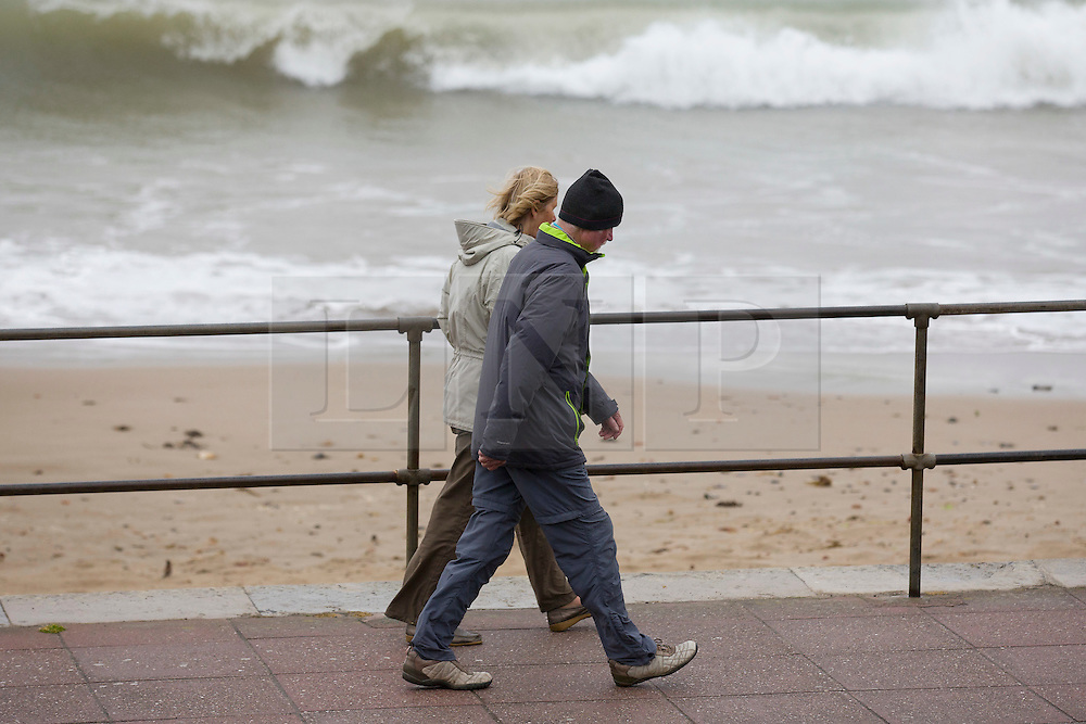 © London News Pictures. 02/06/2015. United Kingdom, Swanage. Two people wrapped up for a walk. Grey skies cover the sky over a windy seafront at Swanage, Dorset, on June 1, 2015. Photo credit: LNP