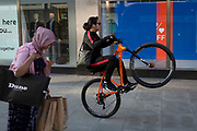 With a further 149 reported dying from Coronavirus in the last 24hrs, taking the UK death toll to 43,320, a youth rides dangerously past a lady shopper on Oxford Street, during the Covid pandemic. As the public stayed at home, young riders have been increasingly riding in large groups through West End streets and on pavements, on 25th June 2020, in London, England.