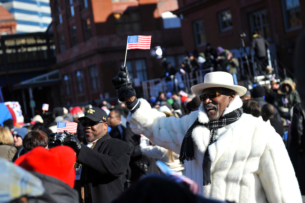 Donning a white fur coat to combat the sub-zero temperatures, a supporter waves a miniature flag during a President-elect Obama pre-inauguration rally in Wilmington, Delaware.  He was one of thousands to attend the event.  Obama, Vice President-elect Biden and their families traveled by train on a Whistle Stop Tour, opening Inauguration celebrations with rallies in Philadelphia, Wilmington, and Baltimore before their final arrival in Washington, D.C.  The inauguration takes place on January 20, 2009, swearing Obama in as the 44th President of the United States of America.¬?