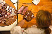 Dolly Irigoyen preparing the roast beef as seen in the overhead instruction mirror, a cutting board with the roast, plates with slices of meat and an assistant distributing the sauce. The Dolly Irigoyen - famous chef and TV presenter - private restaurant, Buenos Aires Argentina, South America Espacio Dolli