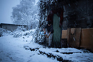 A young man from Afganistan is seen performing ablutions before praying during an heavy snowfall. A group of more than a hundred are living in an abandoned factory in Bihac waiting to try 'the game', as migrants call their attempts to cross the Bosnian Croatian border. January 25, 2021.