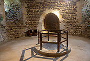 Well and storage space in cellar of 12th century Orford castle, Suffolk, England, UK