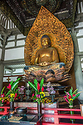 """Inside Byodo-In Temple is a statue of the Lotus Buddha, a large carved wooden image depicting Amida (or Amitabha), a celestial buddha according to the scriptures of Mahayana Buddhism. The Buddha is an original art work by Japanese sculptor Masuzo Inui. The carving was covered with cloth, painted with three coats of gold lacquer, and later coated with gold leaf. The Amida Hall (Amida-do) is also known as the Phoenix Hall (Hoo-do) because of a pair of Chinese phoenix statues on the roof. The hall and its artistry portray the culture of the Fujiwara clan's aristocracy of Japan. The peaceful Byodo-In Temple is in Valley of the Temples Memorial Park, at 47-200 Kahekili Highway, Kaneohe, on the island of Oahu, Hawaii, USA. Byodo-In Temple (""""Temple of Equality"""") was built in 1968 to commemorate the 100 year anniversary of the first Japanese immigrants to Hawaii. This Hawaii State Landmark is a non-practicing Buddhist temple which welcomes people of all faiths. Byodo-In Temple in O'ahu is a half-scale replica of the original Byodo-in Temple built in 1053 in Uji, Japan (a UNESCO World Heritage Site)."""