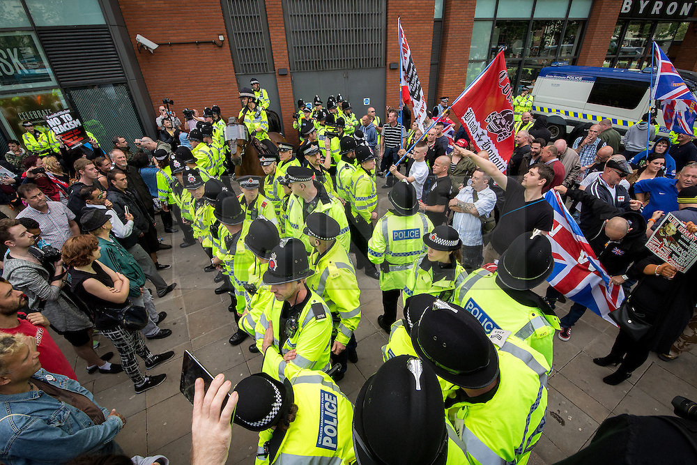 """© Licensed to London News Pictures . 22/08/2015 . Manchester , UK . Police separate anti-fascists and far right protesters . Far-right nationalist group , """" North West Infidels """" and Islamophobic , anti-Semitic and white supremacist supporters , hold a rally in Manchester City Centre . Photo credit : Joel Goodman/LNP"""