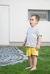 Boy learning to talk and sing outside his house, Bavaria, Germany