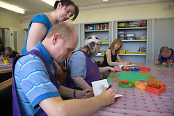 Care Assistant looking on as Service user with learning disability writes his name on a card,