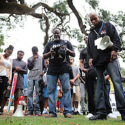 People gather and pray in the rain at Lake Eola park during the Orlando Is Ferguson event in downtown Orlando, Florida on Saturday, August 16, 2014. In light of the recent killing of eighteen year old Mike Brown in Ferguson, Missouri, and the aftermath, citizens are uniting to discuss possible solutions to law enforcement reform and other options for safer police and citizen encounters.  (AP Photo/Alex Menendez)