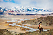 An eagle hunter hunting in the Altai mountains with his golden eagles on horseback, Altai Mountains, Bayan Ulgii, Mongolia