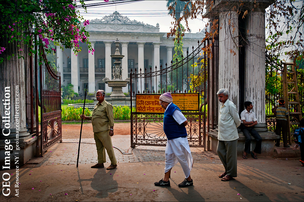 Calcuttans stroll past the Marble Palace, one of the best-preserved family mansions from a bygone era.   Bengali rajas and traders lived in the narrow streets of North Calcutta, where they patronized Indian classical music and the European arts, held lavish feasts, and paid court to the British.