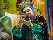 """26 NOVEMBER 2014 - BANGKOK, THAILAND: A Chinese opera performance at the Chow Su Kong Shrine in the Talat Noi neighborhood of Bangkok. Chinese opera was once very popular in Thailand, where it is called """"Ngiew."""" It is usually performed in the Teochew language. Millions of Chinese emigrated to Thailand (then Siam) in the 18th and 19th centuries and brought their culture with them. Recently the popularity of ngiew has faded as people turn to performances of opera on DVD or movies. There are about 30 Chinese opera troupes left in Bangkok and its environs. They are especially busy during Chinese New Year and Chinese holidays when they travel from Chinese temple to Chinese temple performing on stages they put up in streets near the temple, sometimes sleeping on hammocks they sling under their stage.      PHOTO BY JACK KURTZ"""
