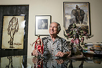 Jim Sullos, President of Edgar Rice Burroughs Inc., with a portrait of Burroughs over his shoulder, poses with figures of John Carter and Tars Tarkas in the office in Tarzana, CA. July 16, 2015. . Photo by David Sprague