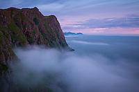 Summer ocean fog dritfs over mountains of Skolmen at midnight, Unstad, Vestvågøy, Lofoten Islands, Norway