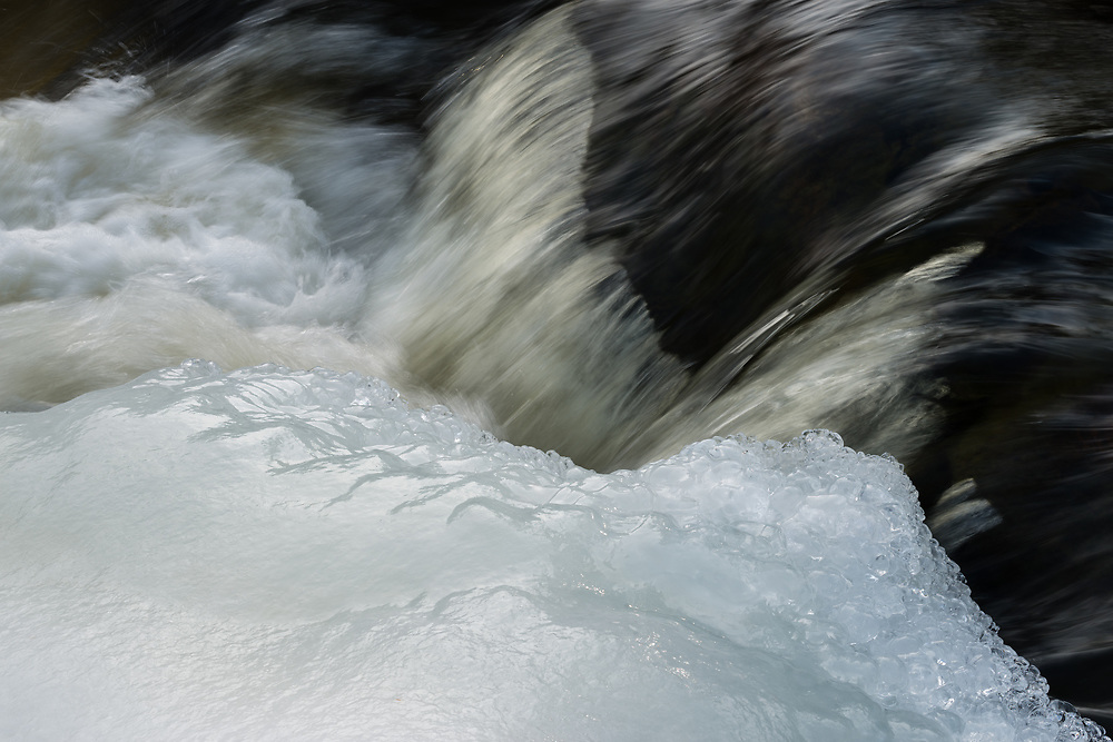 Eels Creek a long flowing waterfall in the Kawarthas was a place I frequented around 15 times from November to April. I enjoyed photographing the changes in flow and the formation of ice as the seasons changed and the light levels also were in a state of daily and seasonal flux. Visiting the same location might seem boring to some, yet getting to know a location can be beneficial to making better photographs. Persistence leads to a better understanding of a location and a better understanding of where to position your camera. This small cascade of water in this photo is framed by shining newly formed ice. The water shows detail in the diffused light and the ice has a very slight reflection.
