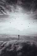 Person standing in a landscape made of clouds - surreal photo manipulation