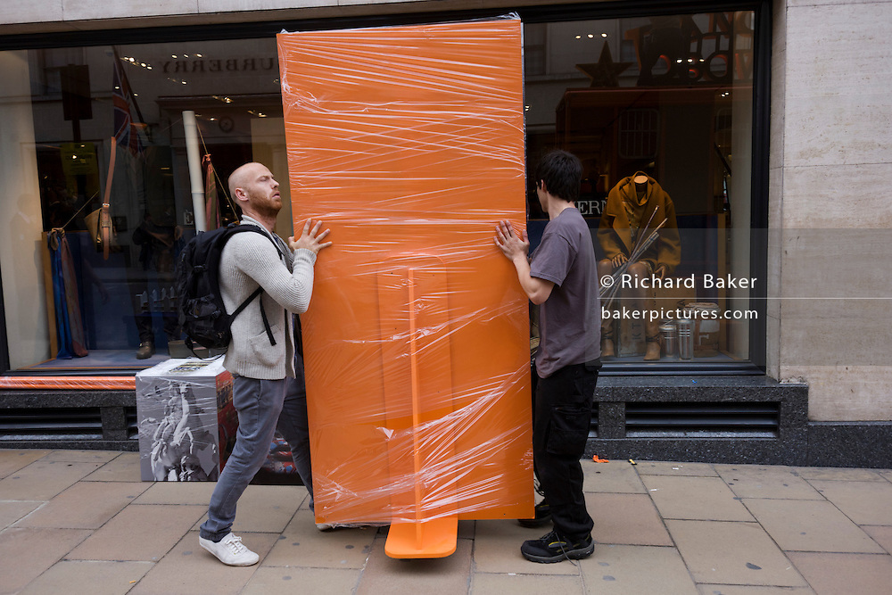 Workman manhandle an orange prop for the Hermes fashion house in London's Bond Street during a Vogue festival.