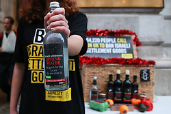 """London, UK. 3rd December, 2018. Campaigners from Amnesty International take a Christmas hamper of """"Israeli stolen goods"""" including red wine, olive oil, honey, mineral water, eggs, dates, peppers, oranges and avocados to the Foreign Office to draw attention to the fact that these goods are all currently being produced in Israel's unlawful settlements in the occupied Palestinian West Bank and to call on governments around the world to ban the importation of Israeli settlement goods. All countries have a clear obligation to ensure respect for international humanitarian law and shouldn't recognise or assist the illegal situation that Israel's settlement policy has created."""