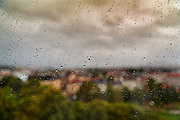 A blurred cityscape on a wet day through a glass window covered in raindrops on 20th September 2019, in Oslo, Norway.