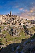 """Long view across """"la Gravina"""" ravine to the Sassi of Matera at sunrise, Basilicata, Italy. A UNESCO World Heritage site.<br /> <br /> The area of Matera has been occupied since the Palaeolithic (10th millennium BC) making it one of the oldest continually inhabited settlements in the world. <br /> The town of Matera was founded by the Roman Lucius Caecilius Metellus in 251 BC and remained a Roman town until  was conquered by the Lombards In AD 664 becoming part of the Duchy of Benevento.  Matera was subject to the power struggles of southern Italy coming under the rule of the Byzantine Roman, the Germans and finally Matera was ruled by the Normans from 1043 until the Aragonese took possession in the 15th century. <br /> <br /> At the ancient heart of Matera are cave dwellings known as Sassi. As the fortunes of Matera failed the sassy became slum dwelling and the appalling living conditions became be the disgrace of Italy. From the 1970's families were forcibly removed from the Sassi and rehoused in the new town of Matera. Today tourism has regenerated Matera and the sassi have been modernised and are lived in again making them probably the longest inhabited houses in the world dating back 9000 years. .<br /> <br /> Visit our ROMAN ART & HISTORIC SITES PHOTO COLLECTIONS for more photos to download or buy as wall art prints https://funkystock.photoshelter.com/gallery-collection/The-Romans-Art-Artefacts-Antiquities-Historic-Sites-Pictures-Images/C0000r2uLJJo9_s0<br /> .<br /> <br /> Visit our MEDIEVAL PHOTO COLLECTIONS for more   photos  to download or buy as prints https://funkystock.photoshelter.com/gallery-collection/Medieval-Middle-Ages-Historic-Places-Arcaeological-Sites-Pictures-Images-of/C0000B5ZA54_WD0s"""