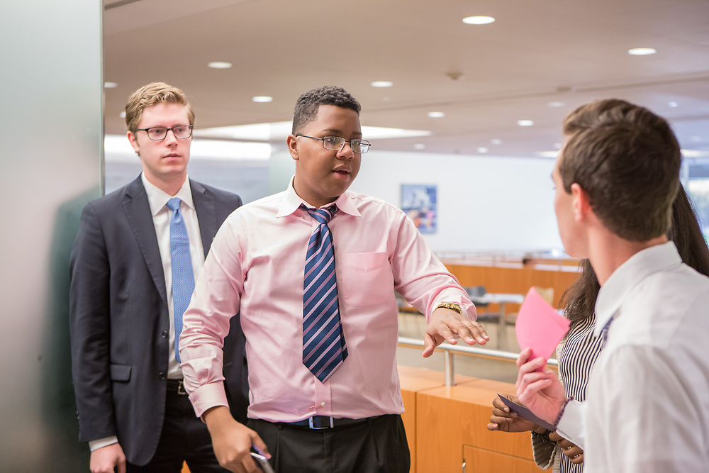 Purchase, NY – 31 October 2014. White Plains High School team member Frank Marte talking to a team member as Morgan Stanley facilitator Craig Styles looks on. White Plains High School went on to take first place in the 2014 competition. The Business Skills Olympics was founded by the African American Men of Westchester, is sponsored and facilitated by Morgan Stanley, and is open to high school teams in Westchester County.
