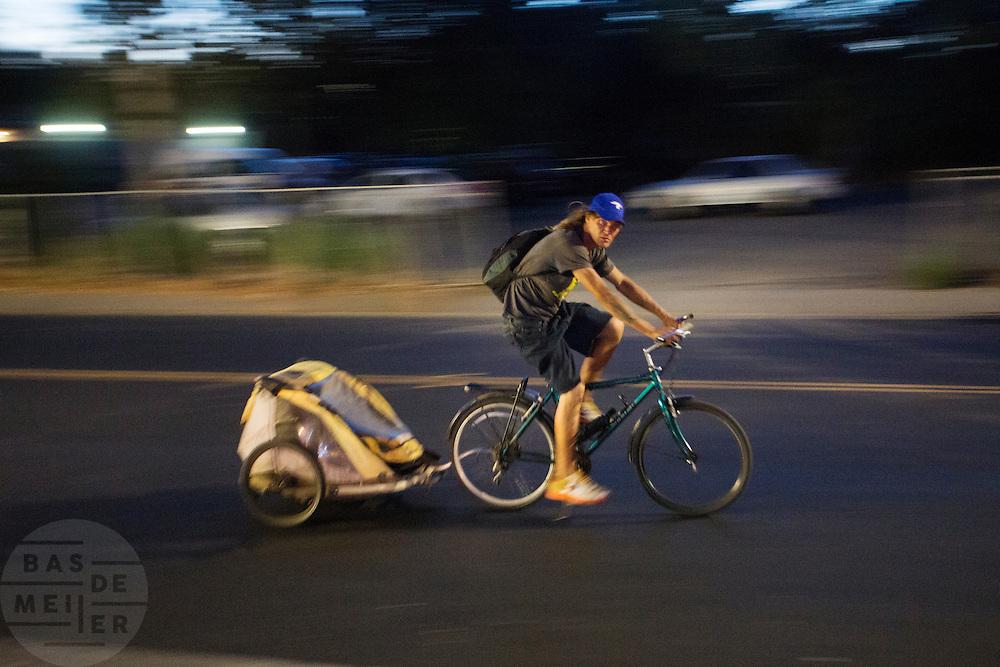 In de Amerikaanse plaats Davis, California fietst een man met een fietskar door de avond.<br /> <br /> In the American town Davis, California cyclists ride in the evening with a trailer.