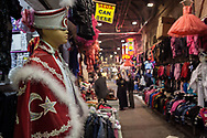 Traditional circumcision ceremony costumes hang alongside dresses in Kayseri's old covered market.
