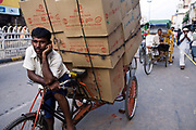 A rickshaw wallah rests on Chadni Chowk with his deliveries. Old Delhi, India