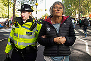 A climate change protester isarrested in Millbank  by the police on 8th October, 2019 in London, Untited Kingdom. Extinction Rebellion plan to occupy 12 sites situated around key Government locations around Westminster for two weeks to protest against climate change.